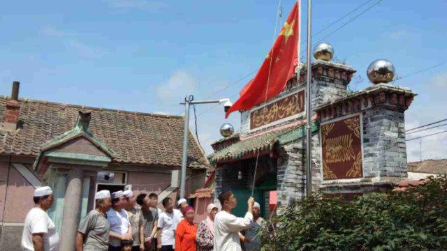 Muslime in einer Moschee werden gezwungen, eine Flaggenzeremonie abzuhalten.