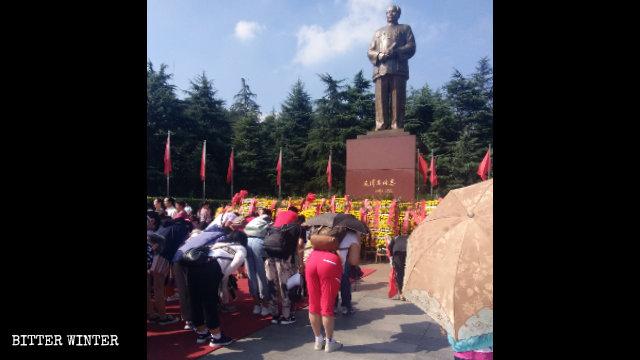 """Touristen verehren vor dem """"Mao Zedong Bronze Statue Square"""""""